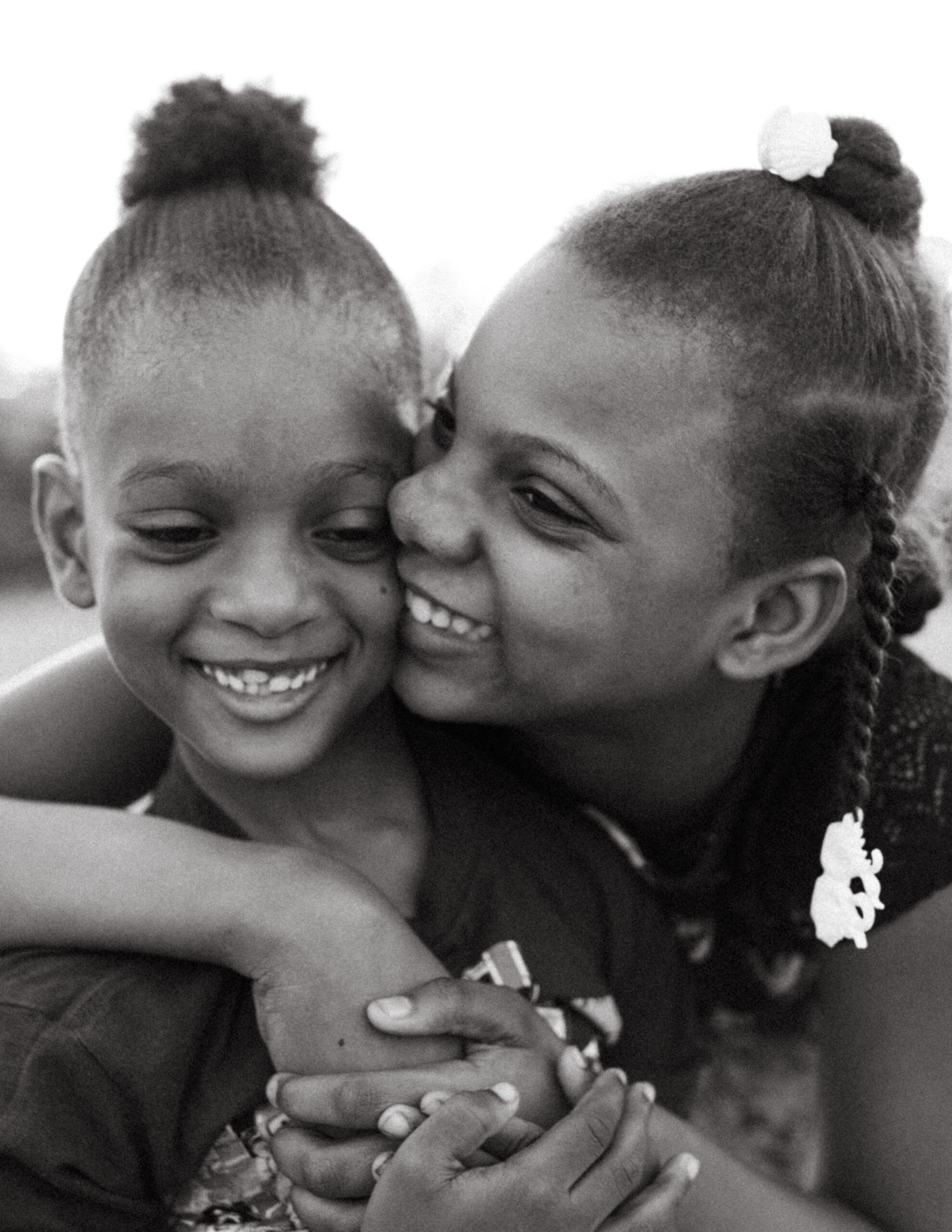 Brother and sister hug one another while laughing in Port-au-Prince, Haiti