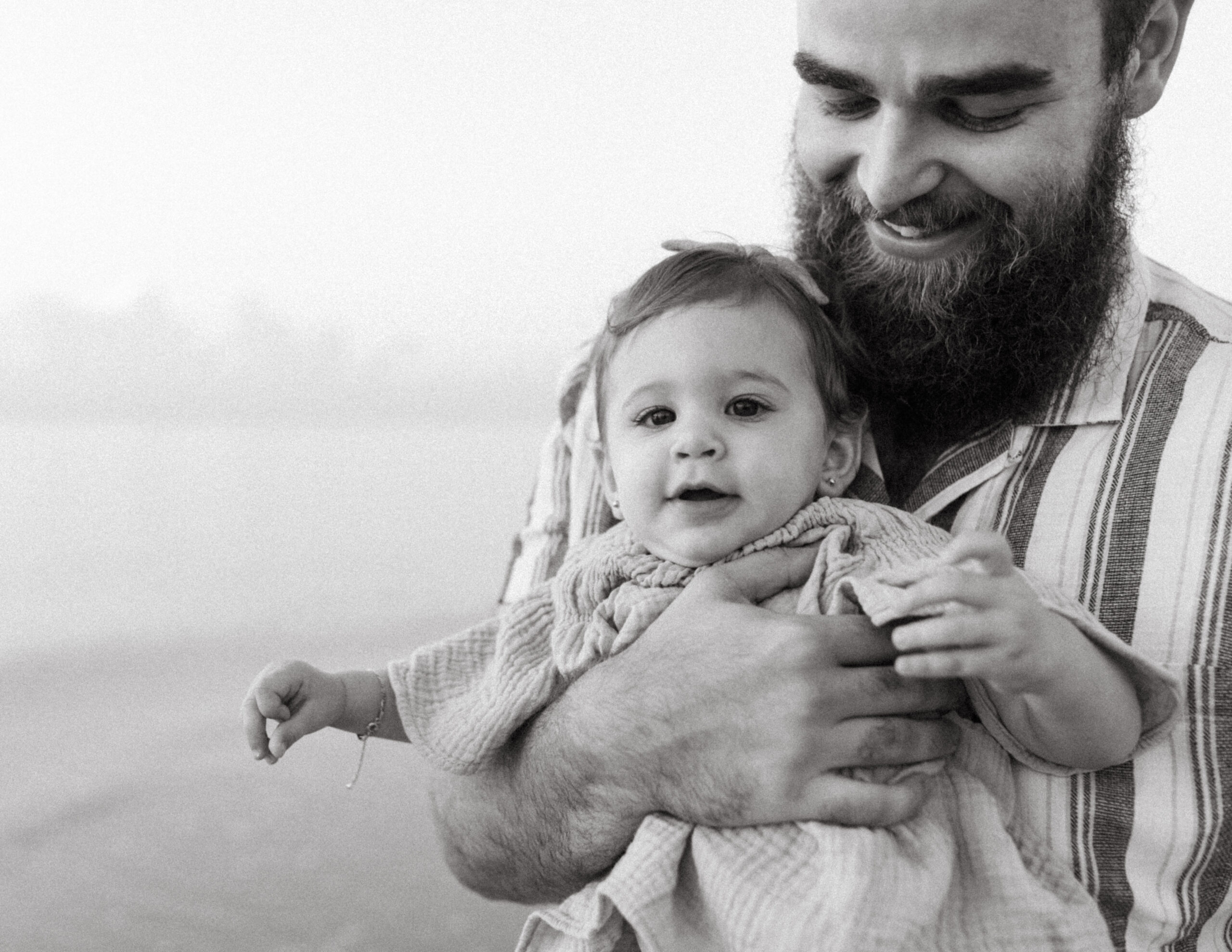Father holds his daughter on the beach at sunrise in Fort Lauderdale, Florida