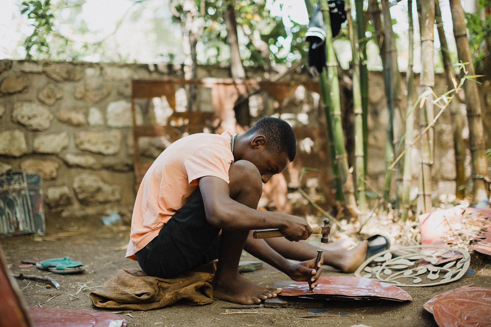 Haitian boys works on tin metal art in Port-au-Prince, Haiti