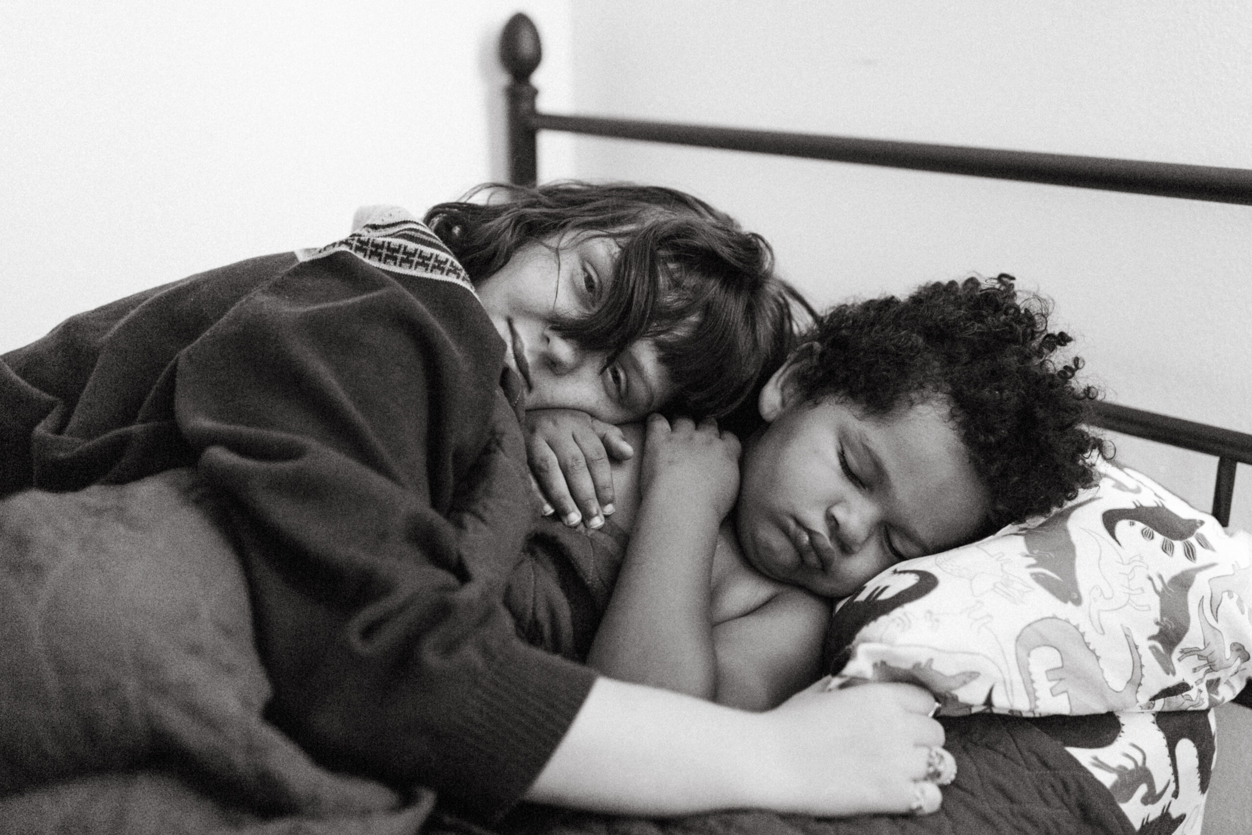 Black and white photo of a sister holding her little brother while he sleeps