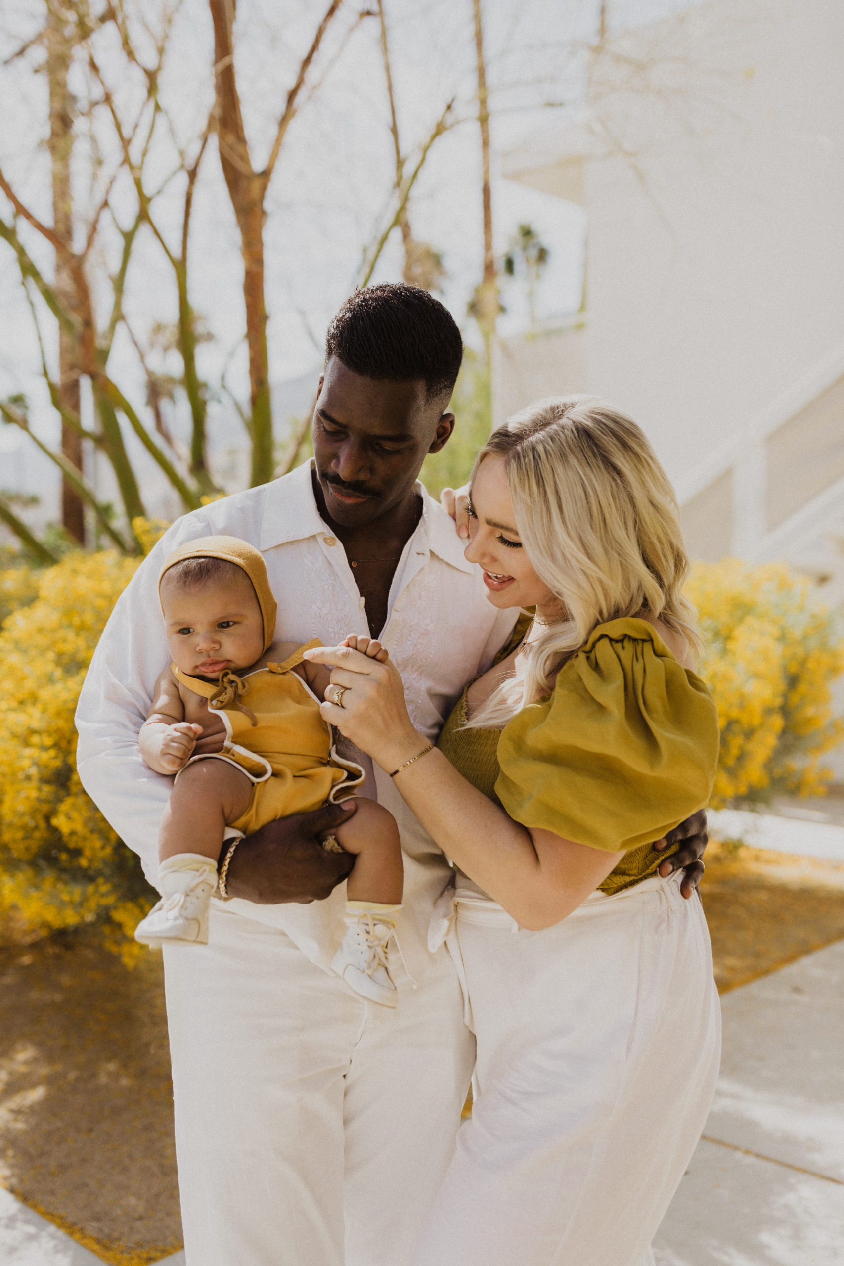 Mixed couple holds their baby at Ace Hotel in Palm Springs, California