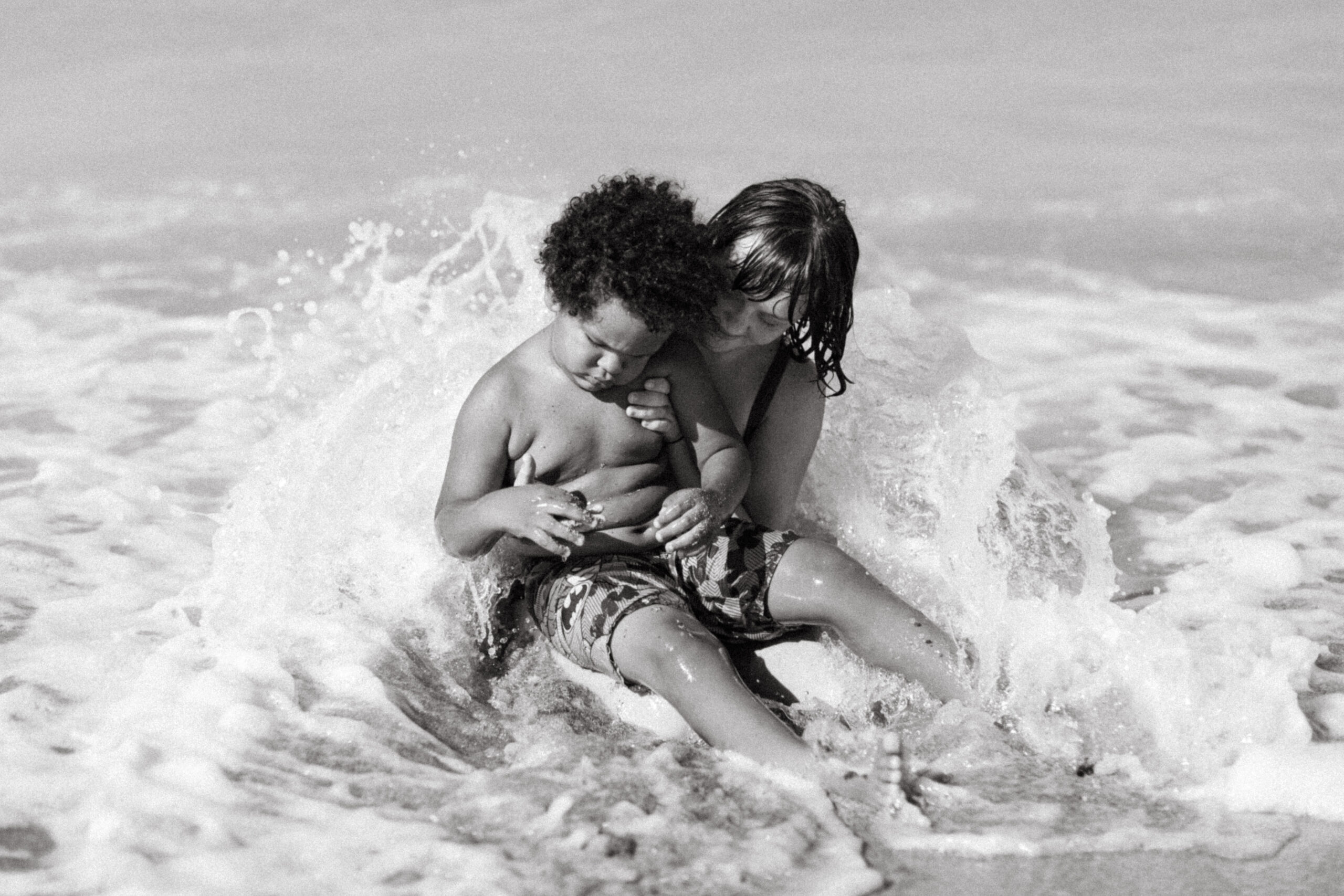 Black and white photo of a sister holding her brother in the ocean