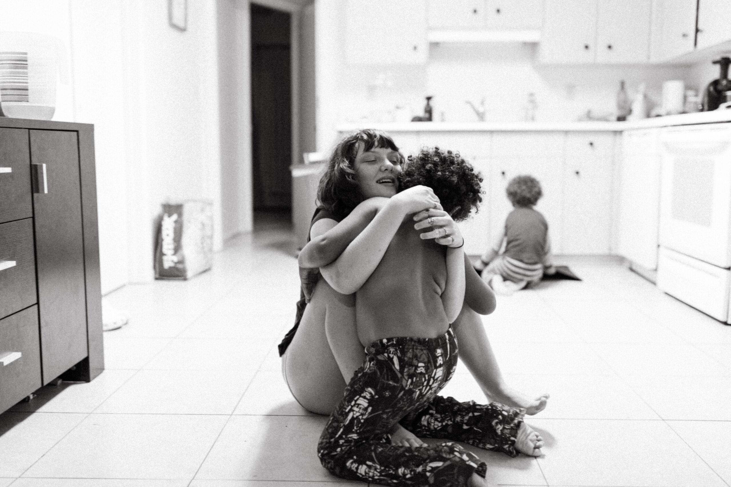 Sister hugs her brother on the kitchen floor