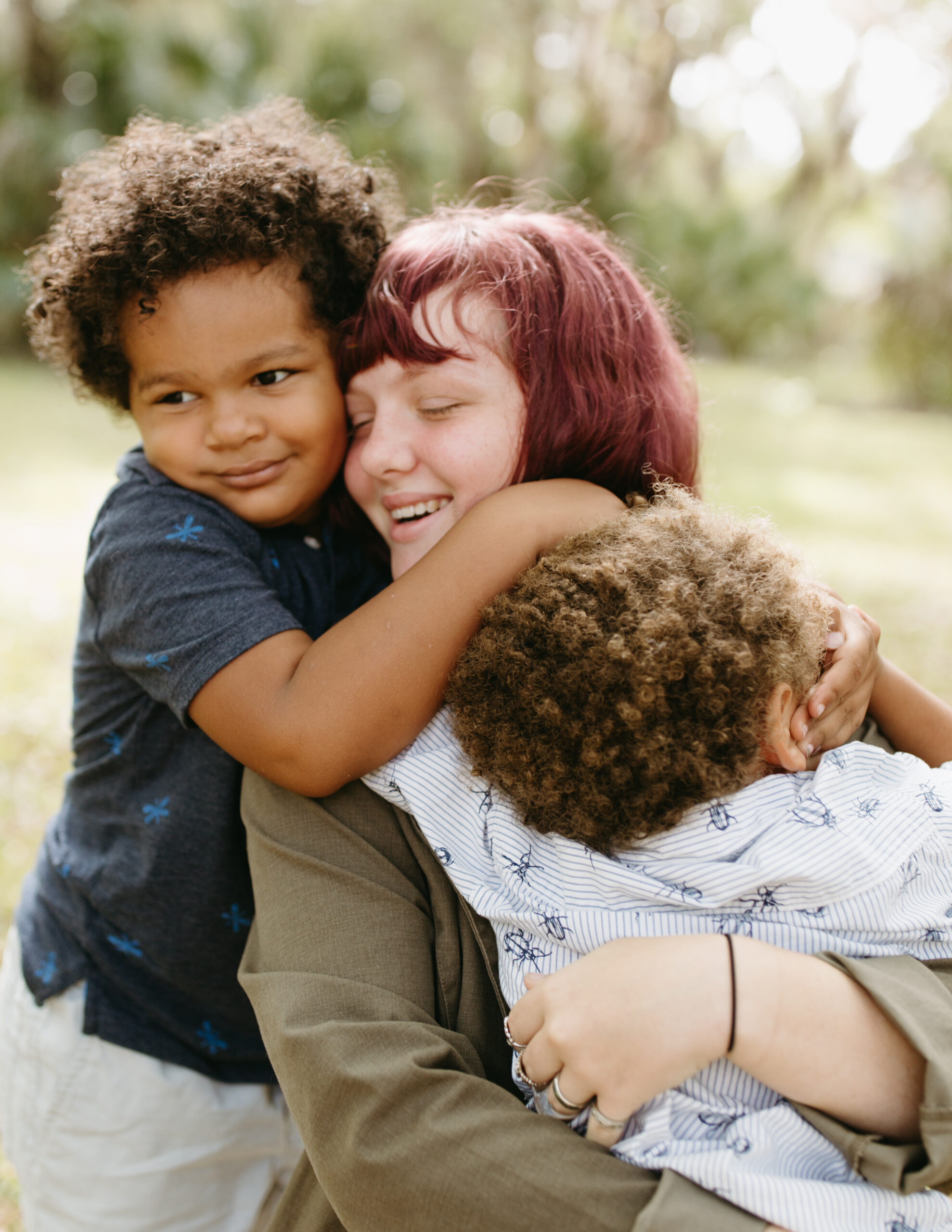 Sister hugs her two younger brothers