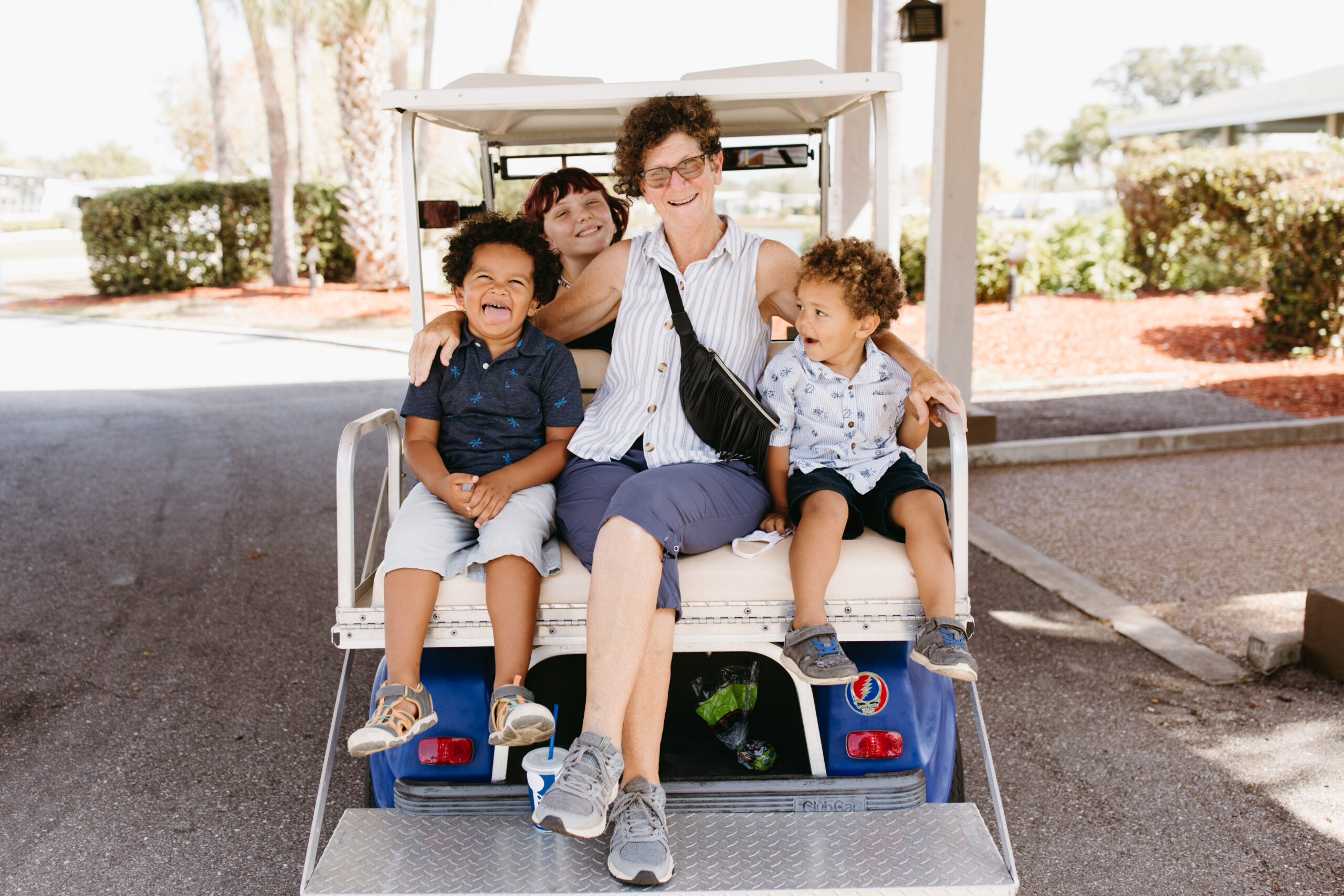 Grandmother rides with her three grandkids in a golf cart in Venice, Florida