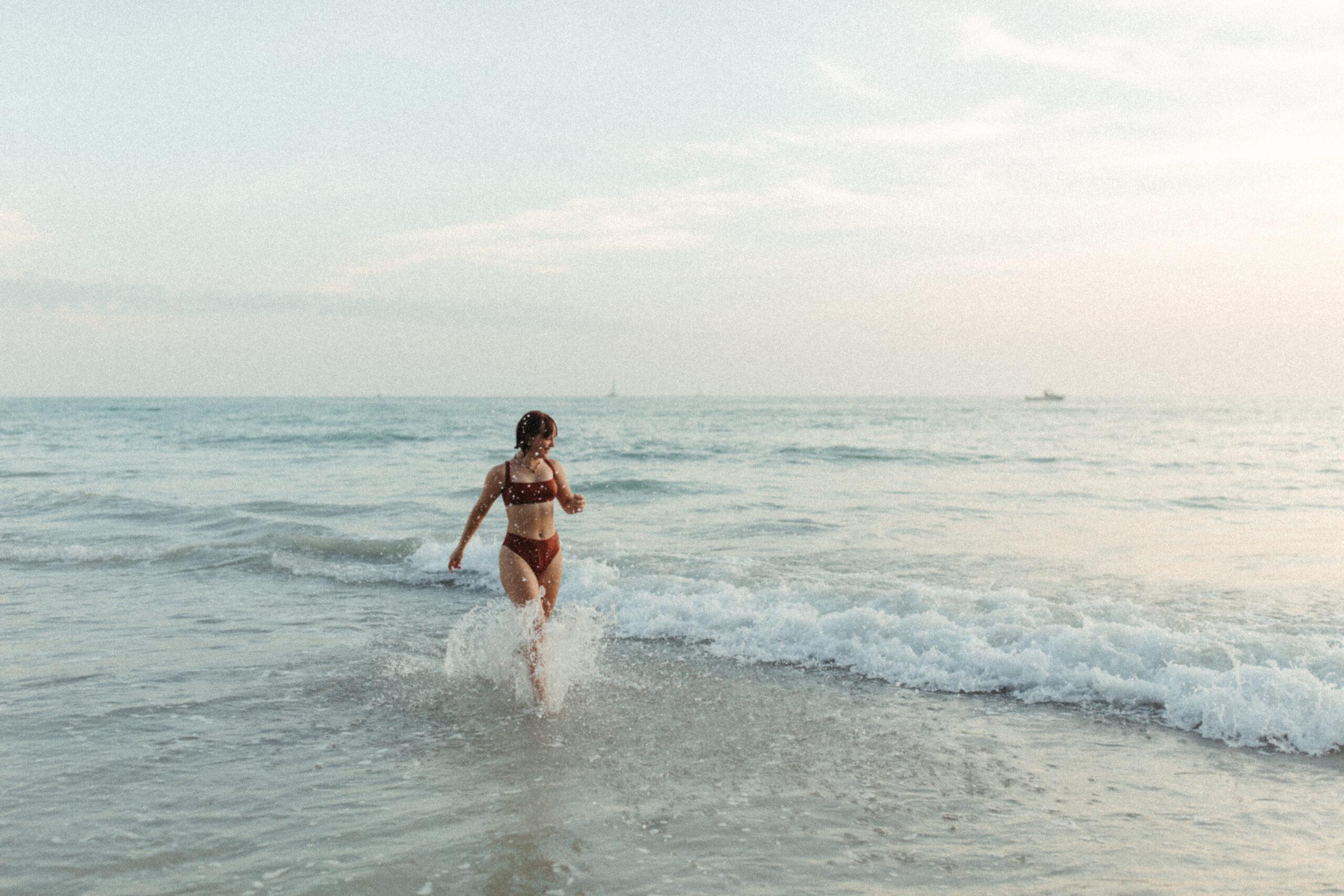 Teenage girl runs in the ocean in Venice Beach, Florida